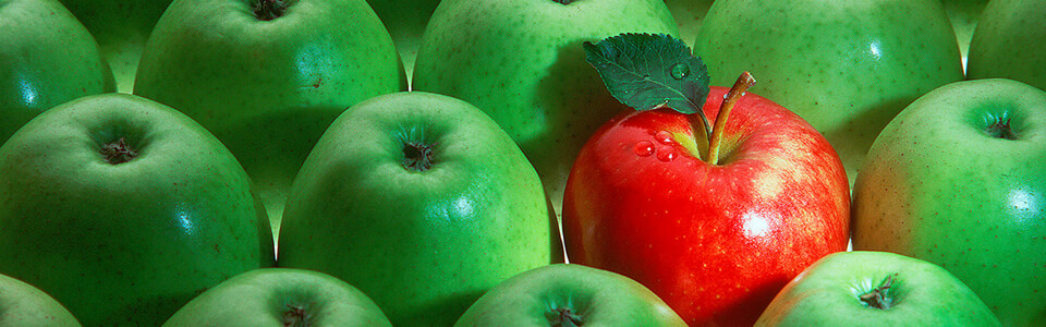 Multiple green apples with one red apple in the middle.