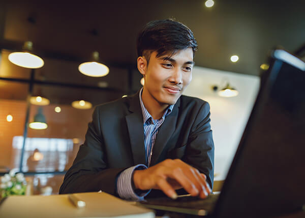 Cheerful young business man with short hair in a black suit jacket typing on a laptop.