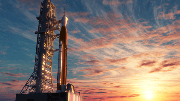 Rocket on a launch pad, during a sunset.