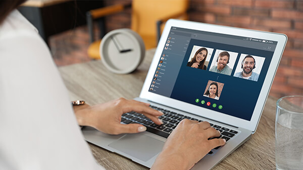 Close-up of a laptop screen showing 4 people on a video call.