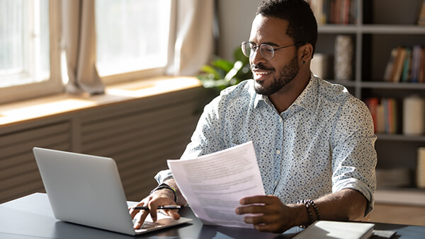 Cheerful man sitting a table, holding documents in his left hand while typing on his laptop with his right hand.