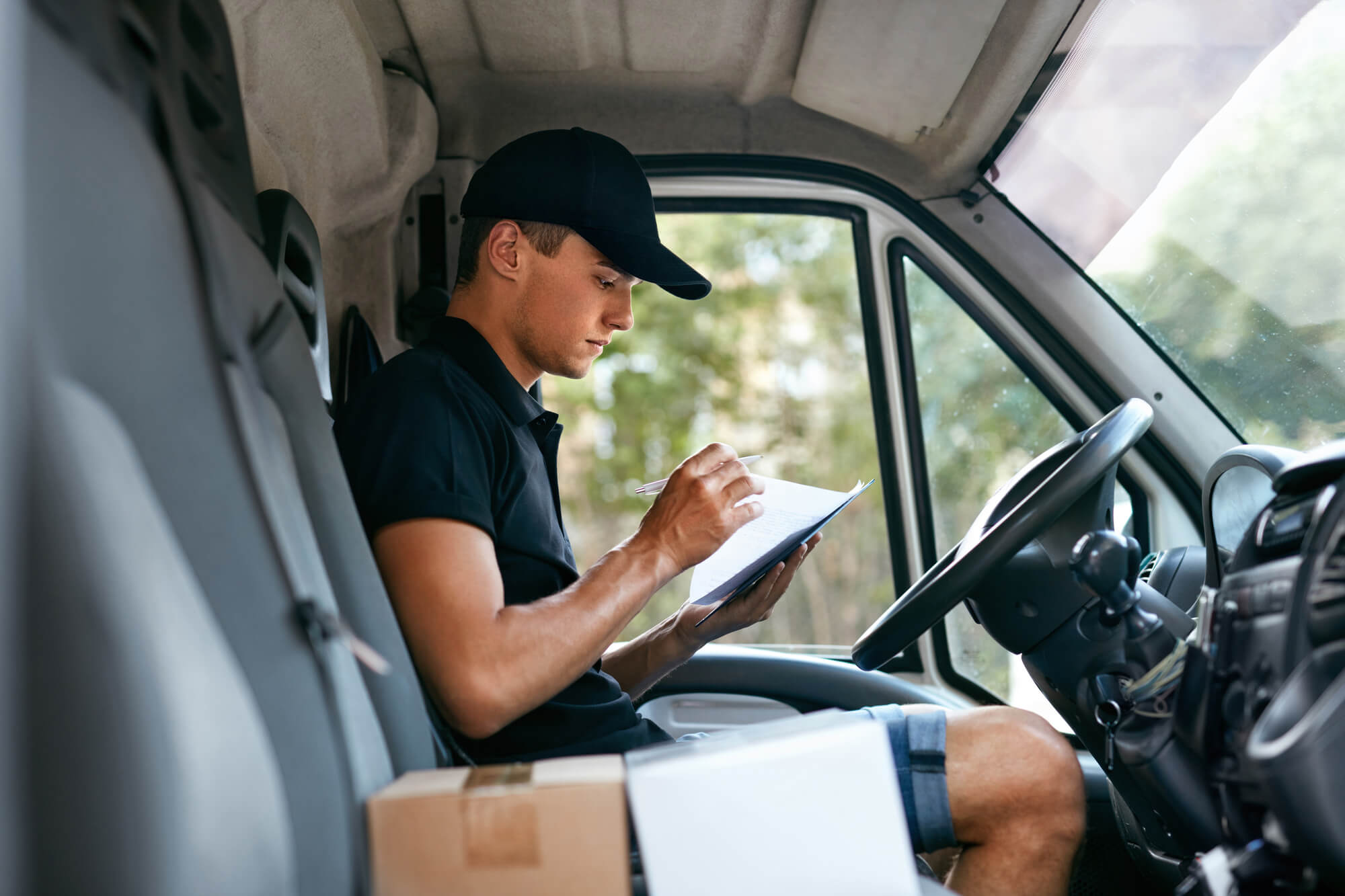 Driver driving truck but distracted by reading something