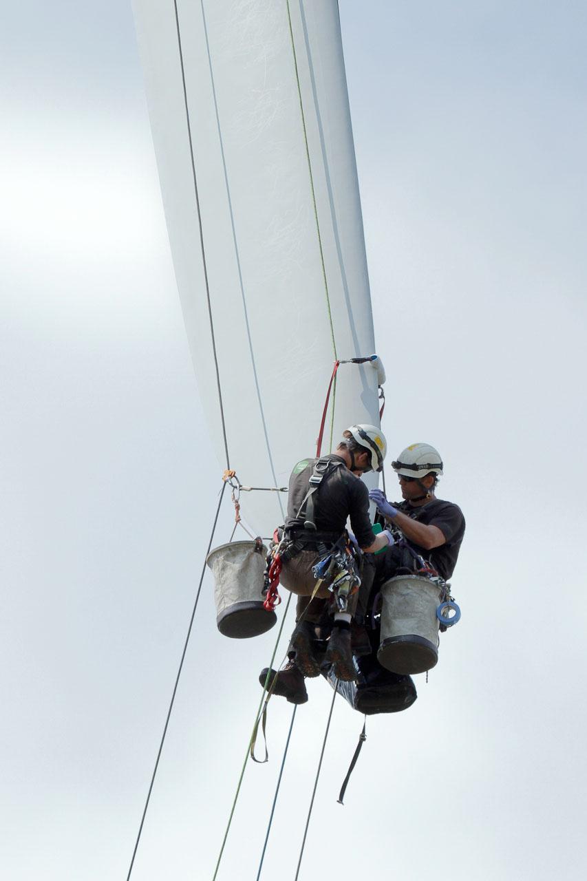 Two technicians repair wind turbine blade tip