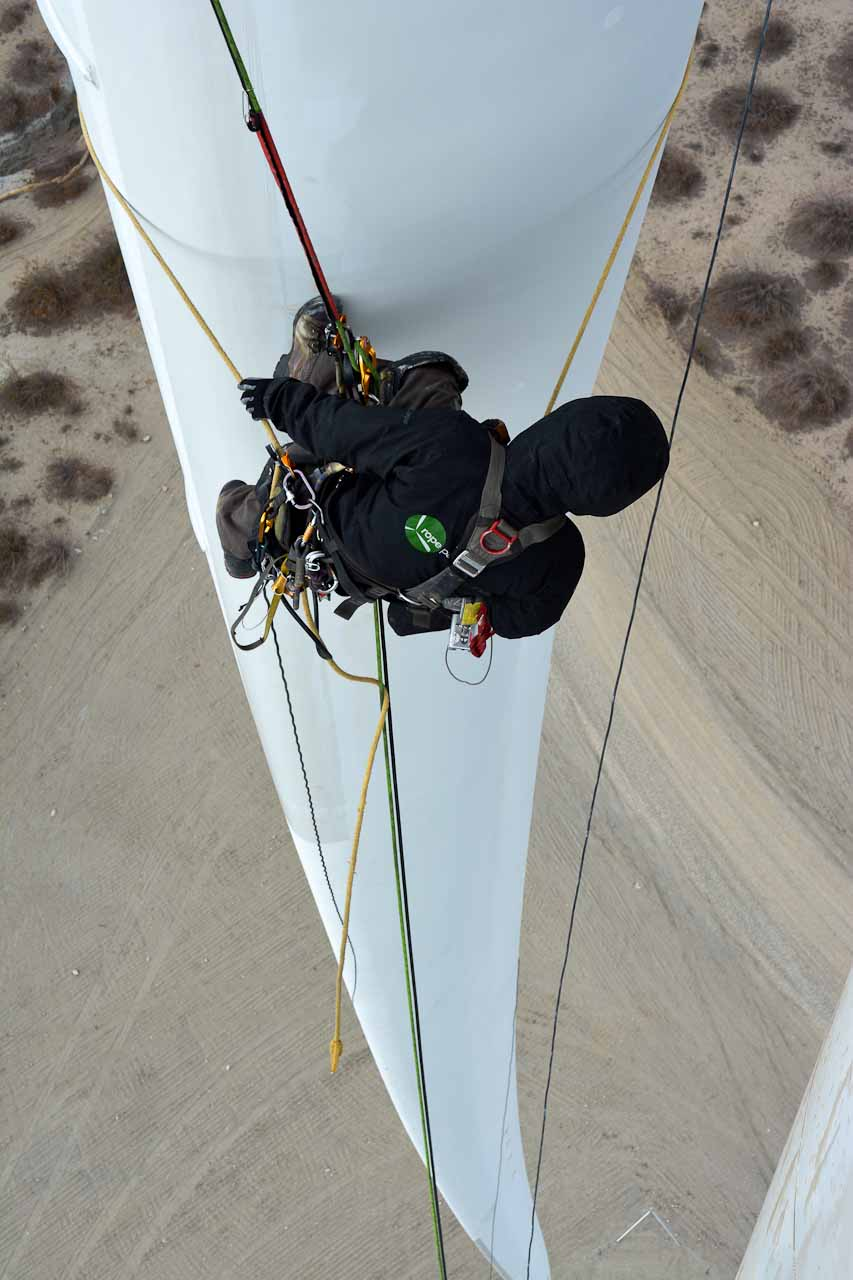 Rope access technician looking down blade edge