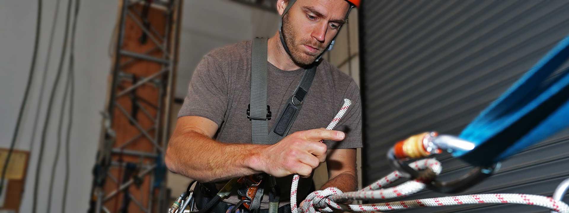 Rope access technician tying knots