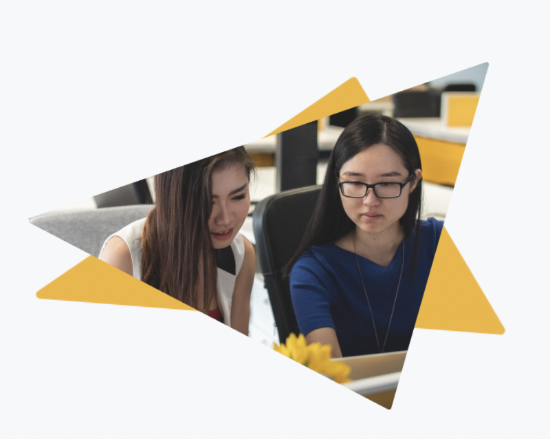 2 women sat at work looking at a computer screen