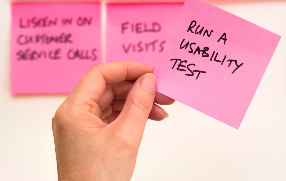 """A photo of someone holding a post-it note that says: """"Run a Usability Test"""""""