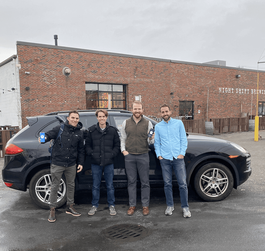 The Openroad team stands outside in front of a car holding up their app on an iPhone screen.
