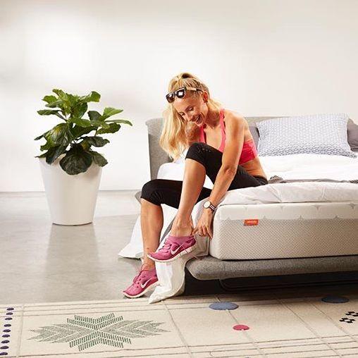 Women putting on running shoes while sitting on Sommuto mattress
