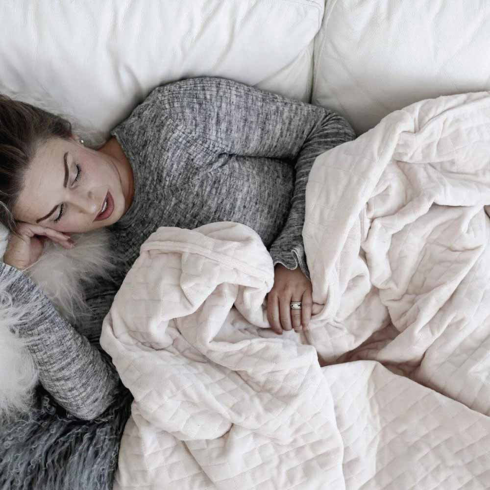 Women laying in bed covered in calming weighted blanket