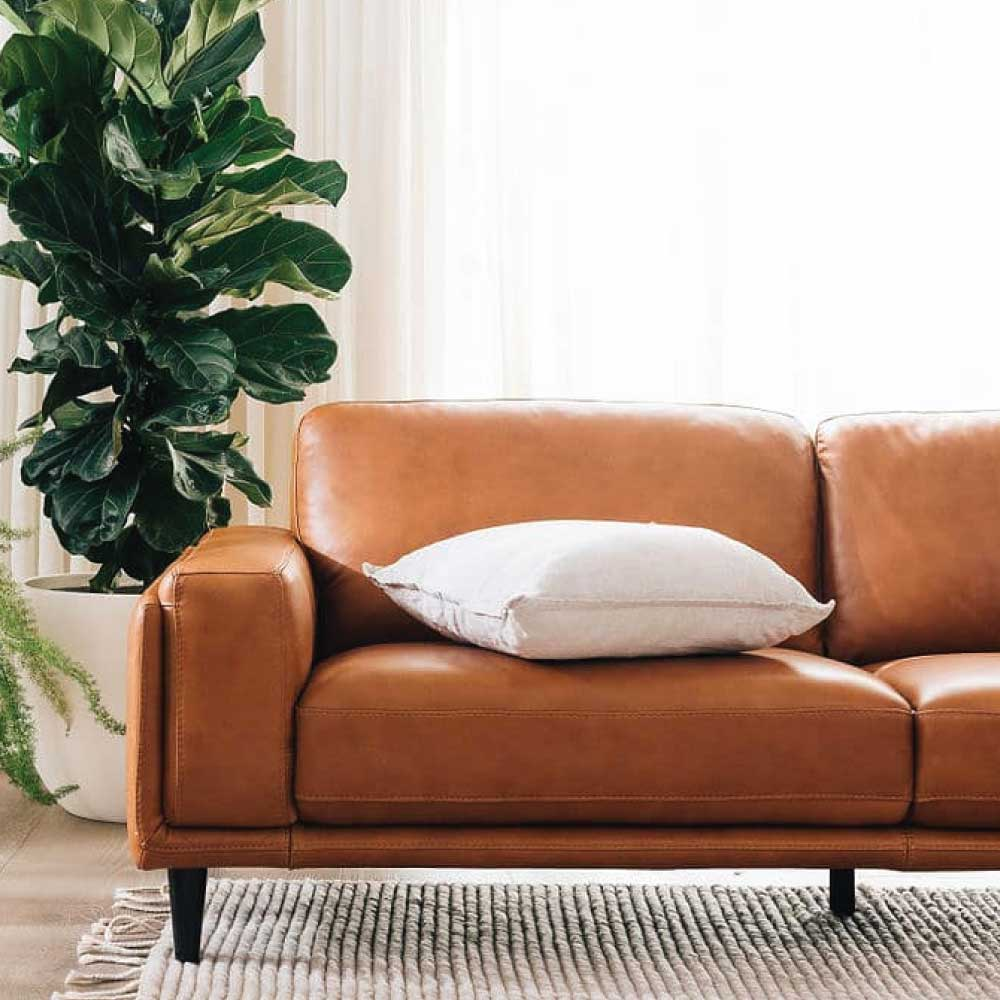 Plush brown leather sofa with white cushion