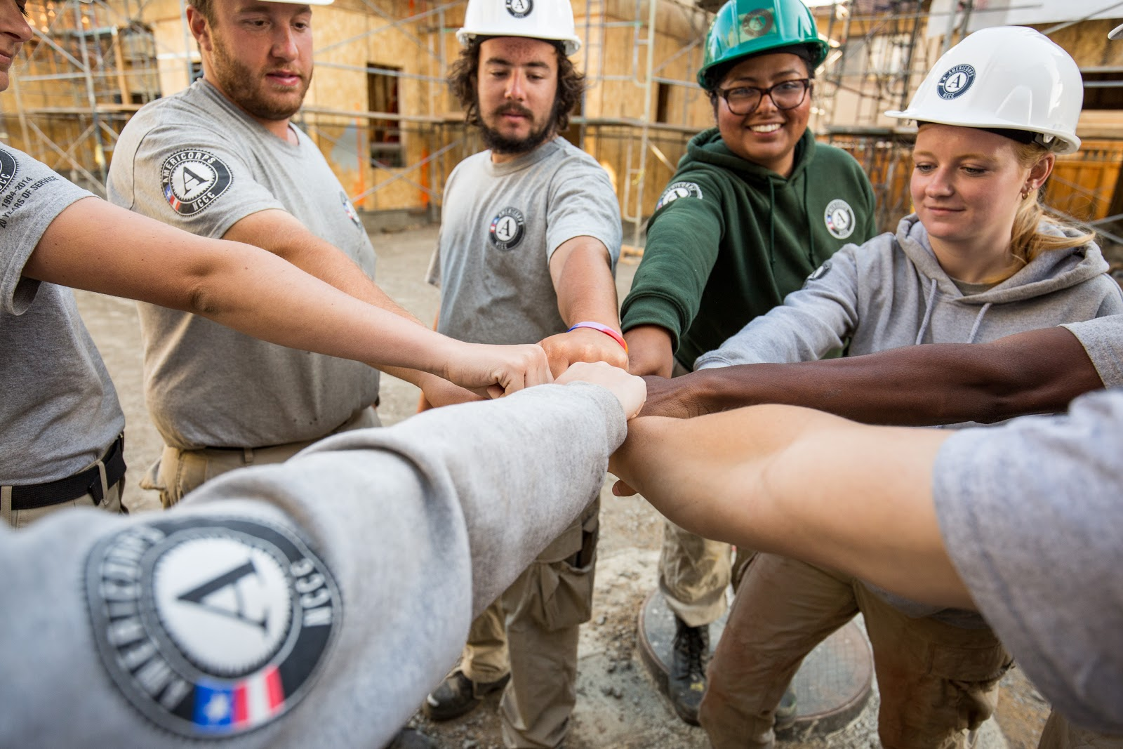 AmeriCorps members stand in a circle with their hands in the middle
