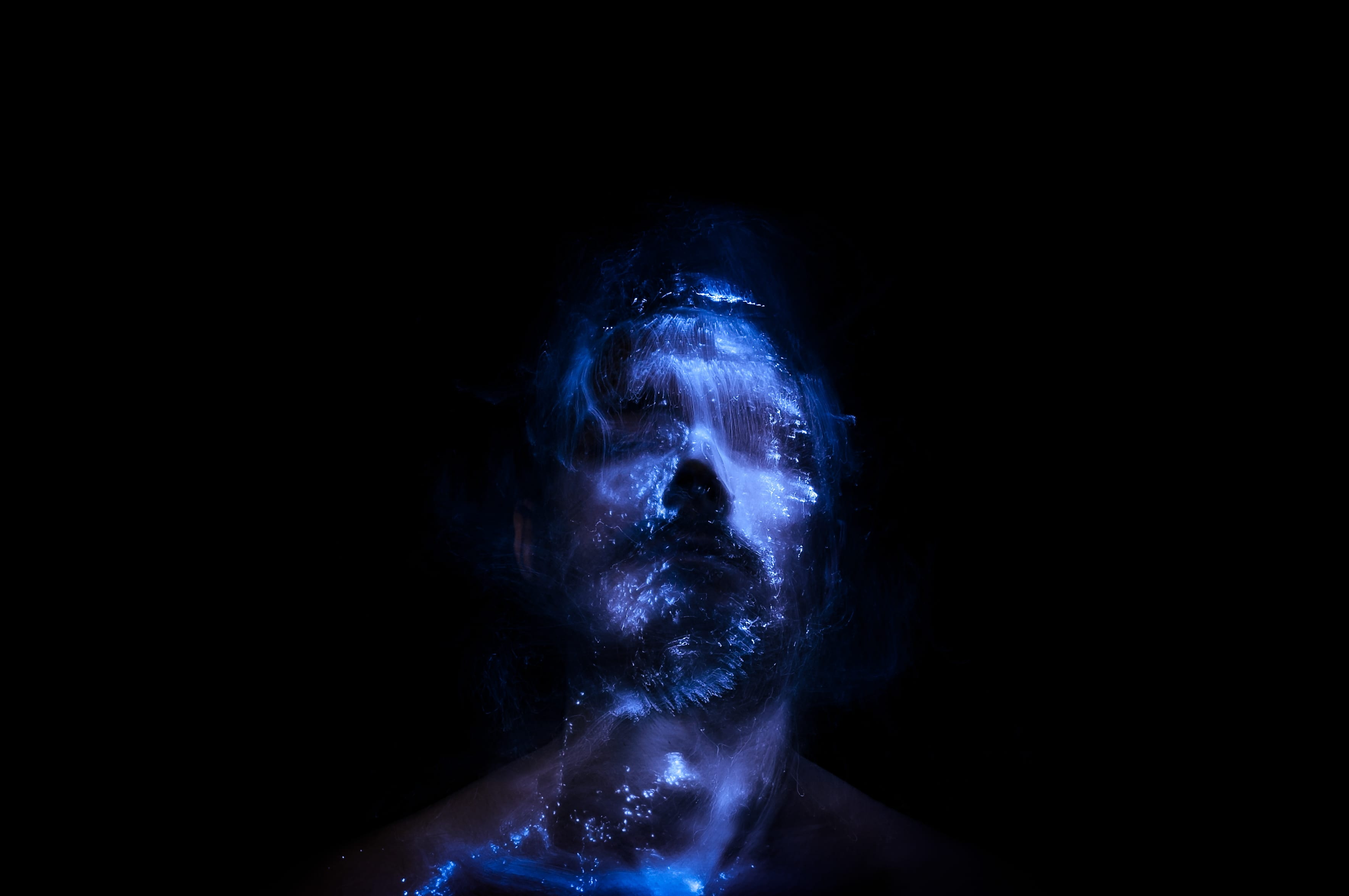Man in dark room with light pinting on his face giving a cyber effect stock photograph by Marco Hartz EyeEm
