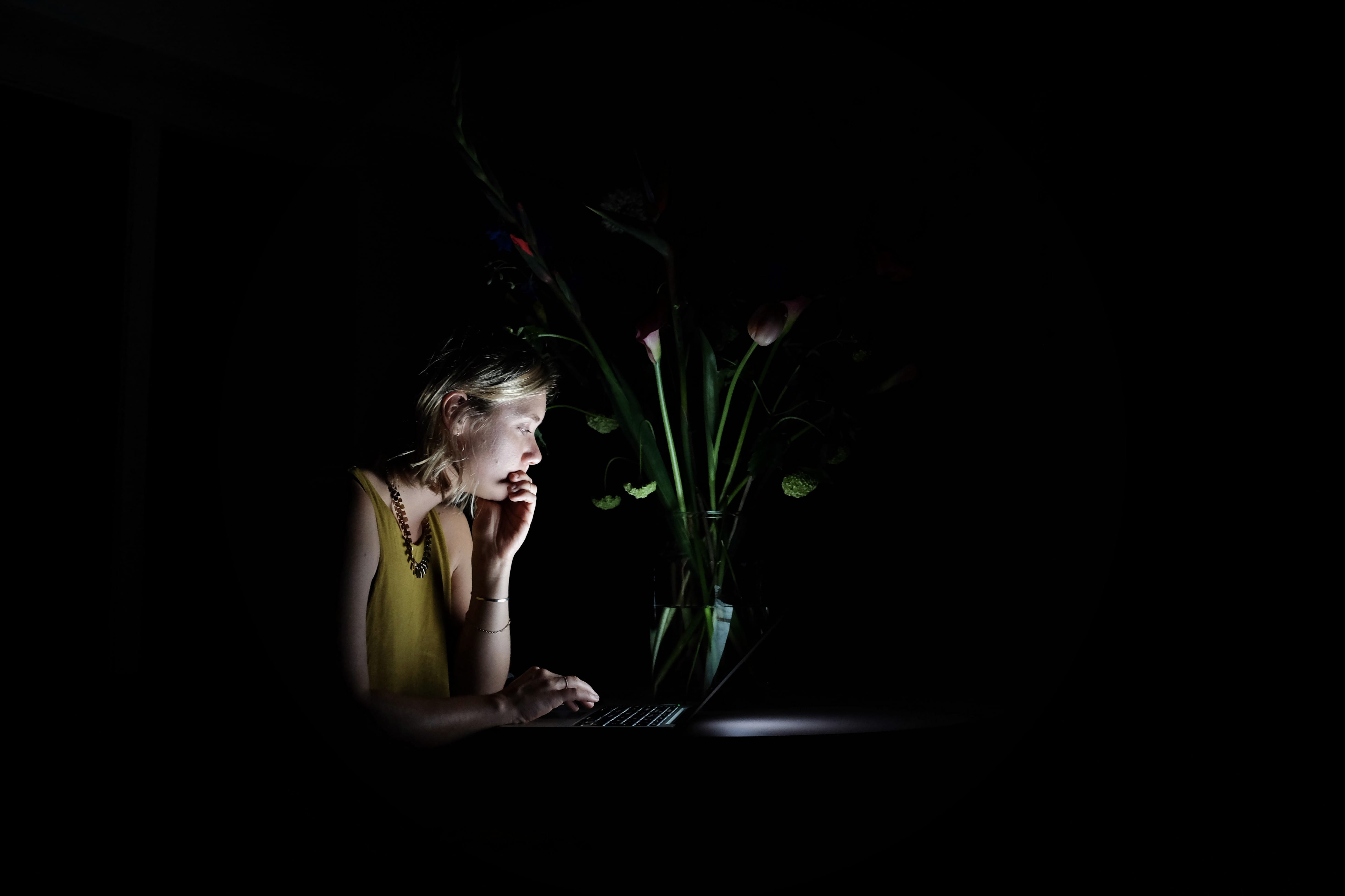 Woman sitting in a dark room using laptop her face is illuminated by the screen stock photograph by Jaime Muñoz EyeEm