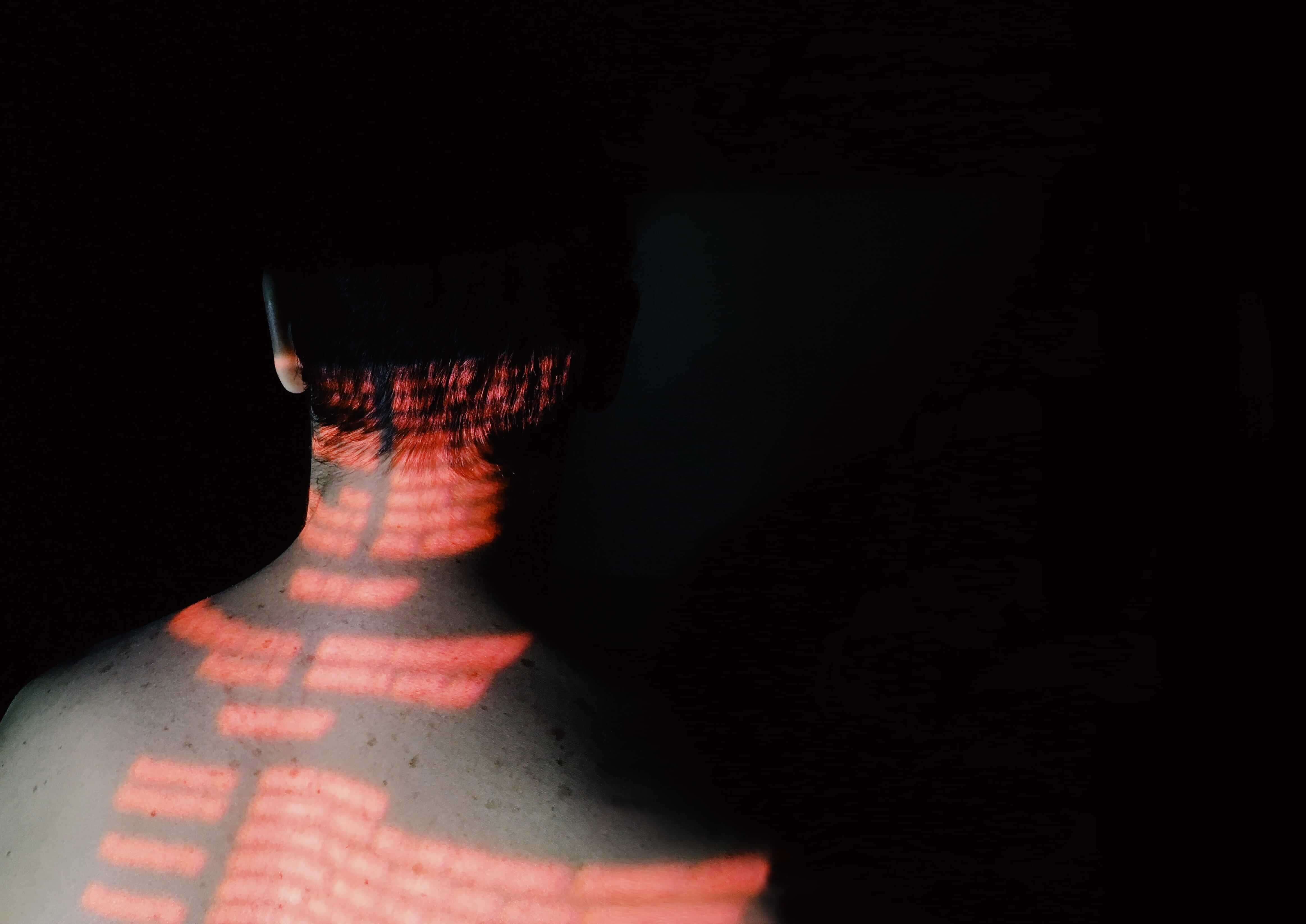 Studio photograph of man with light projection of red text on his back stock photograph by Alina Potapenko EyeEm
