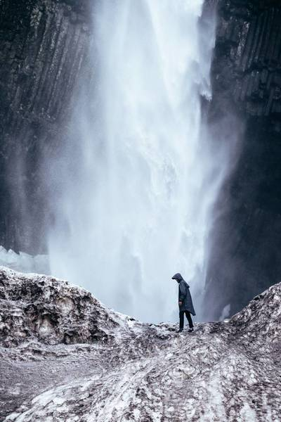Man Standing On Rock By Waterfall In Forest
