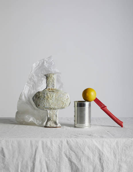 Close-Up Of Stone Vase With Lemon And Knife On Table Against White Background