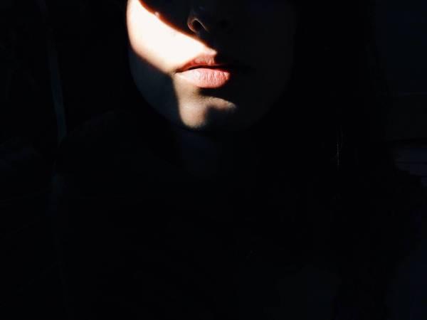 Sunlight falling on lips of woman in darkroom
