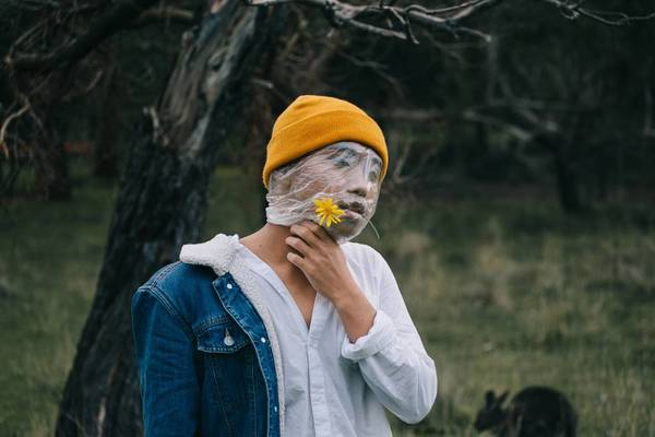 Close-Up Of Young Man Covering Face With Plastic Bag While Holding Flower Outdoors