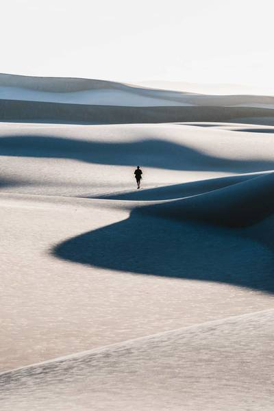Mid Distance View Of Man Walking On Sand Dune