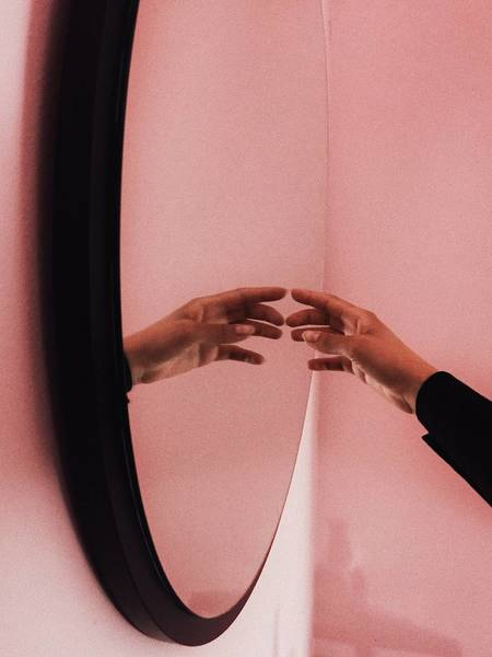 Reflection Of Cropped Hand On Mirror
