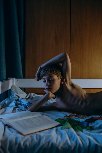 Shirtless Boy Reading Book While Lying On Bed At Home