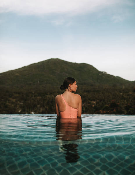 Woman Swimming In Sea Against Mountain