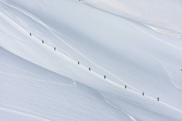 Hikers Walking On Snowcapped Mountain