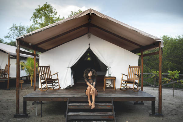 Full Length Portrait Of Woman Sitting Against Tent House