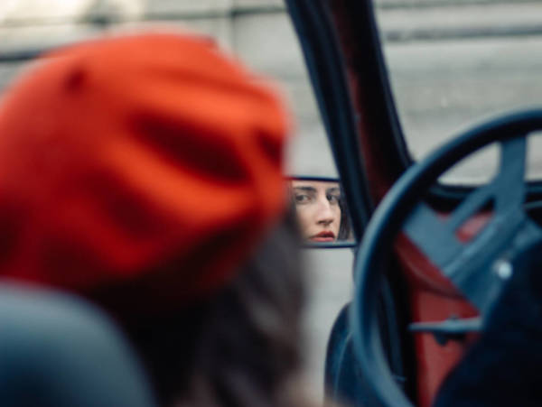 Reflection Of Woman In Car Side-View Mirror