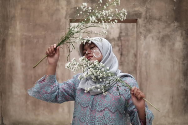 Close-Up Of Muslim Woman Holding Flowers While Standing Against Wall