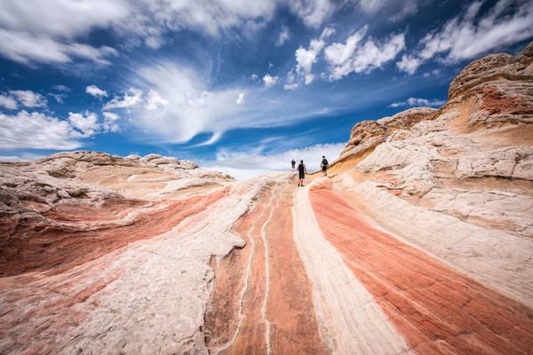 Men Walking On Rock Against Sky