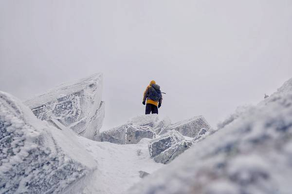 Low Angle View Of Mid Adult Man With Backpack Standing On Snowcapped Mountain Against Sky