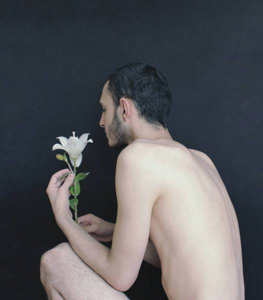 Side View Of Shirtless Young Man Holding Flower While Crouching Against Wall