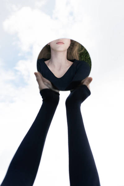 Cropped Hand On Woman Holding Mirror With Reflection Against Sky