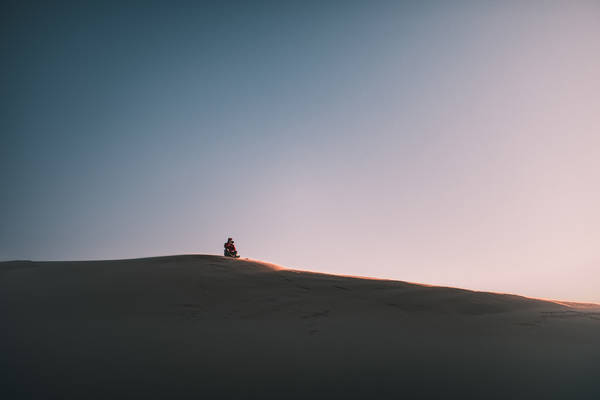 Distant View Of Man Sitting On Sand Dune Against Clear Sky
