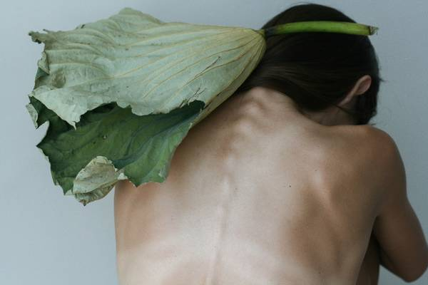 Rear View Of Shirtless Depressed Woman With Leaf Sitting By Wall