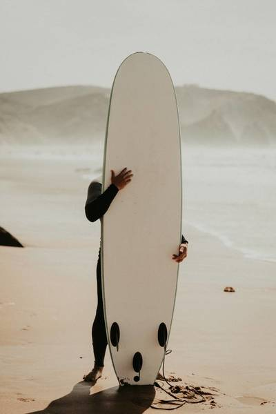 Man Holding Surfboard While Standing On Shore At Beach