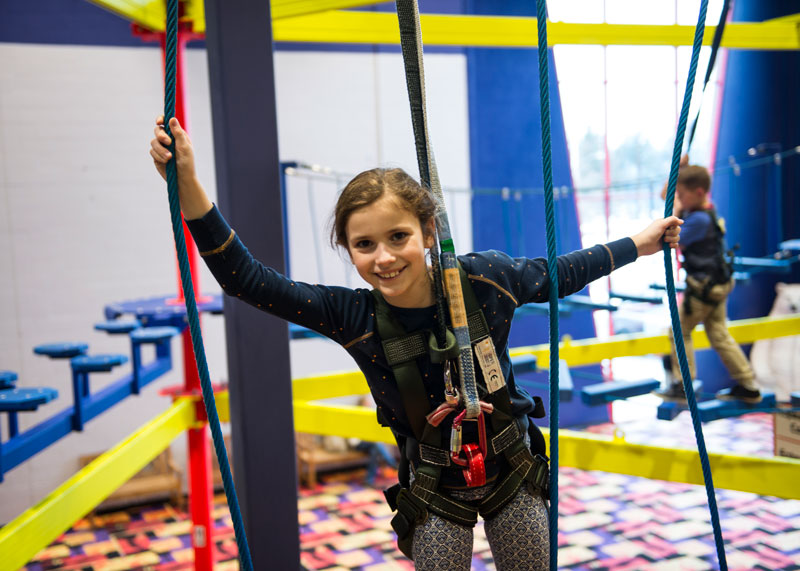 Young girl posing for picture and hanging from ropes