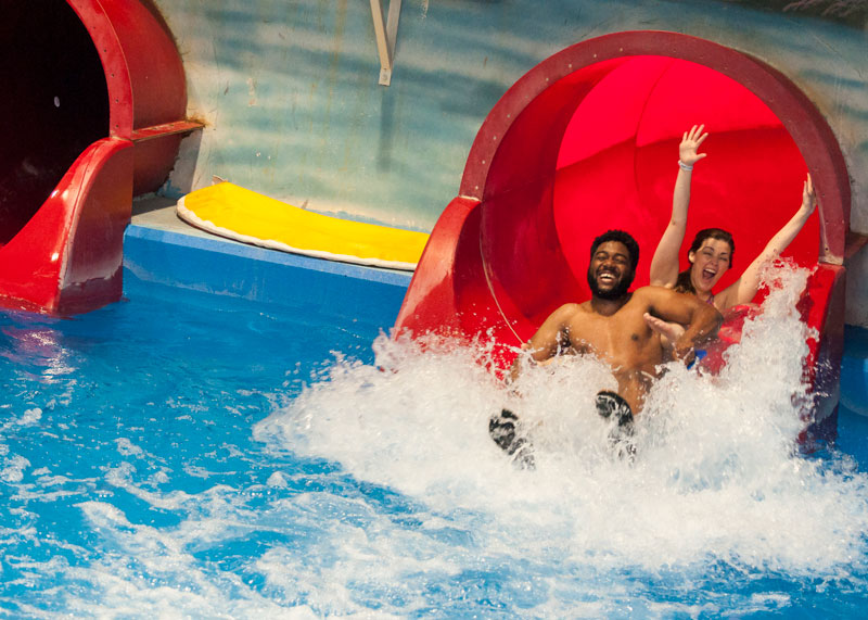 Man and woman sliding down red waterslide