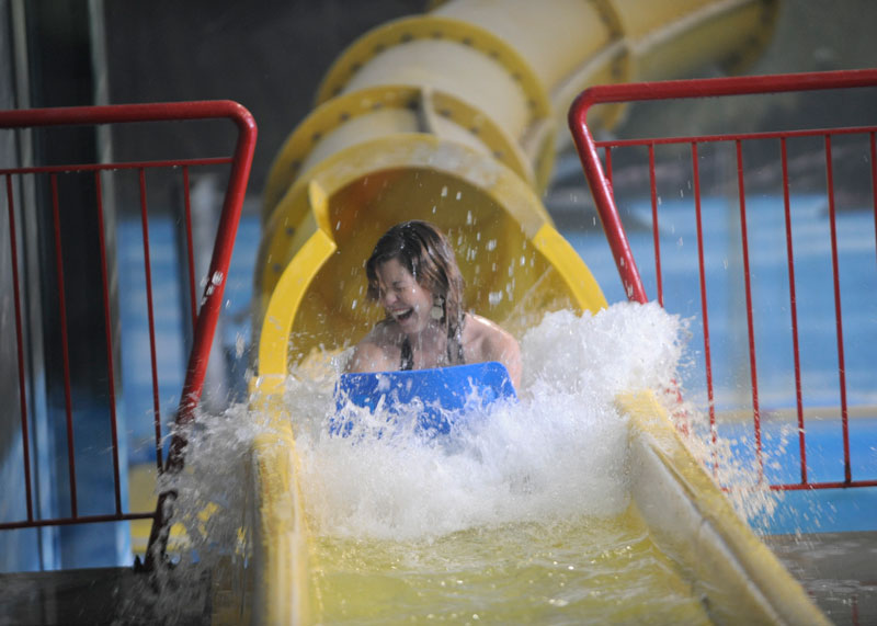 Woman sliding down yellow waterslide on a mat