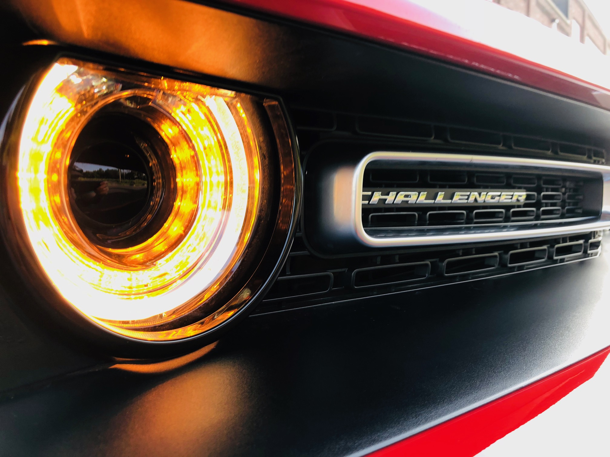 a closeup of the glowing headlight of a cherry red 2018 dodge challenger