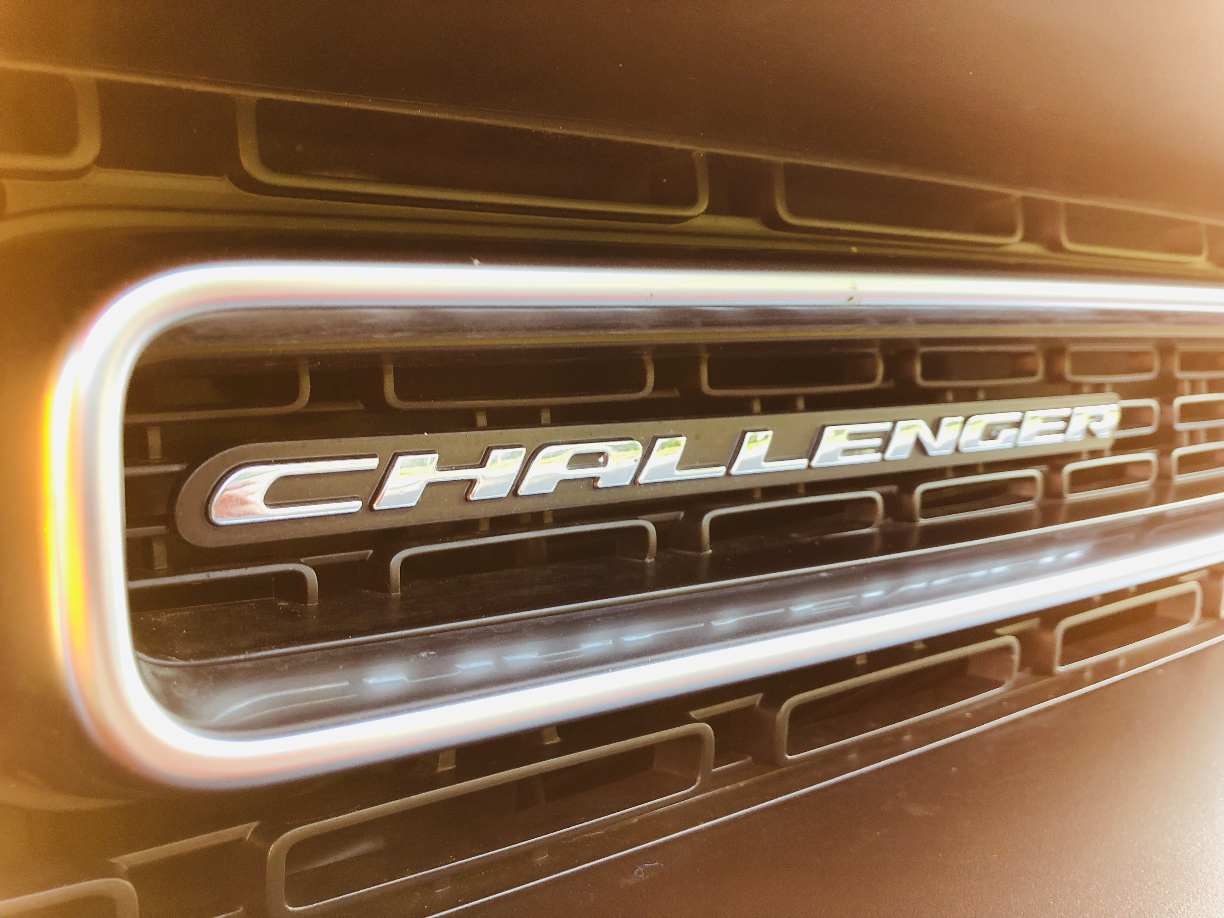 a close up of the challenger plate on the front of a 2018 dodge challenger. The photograph is softened by a yellow-orange lens flare