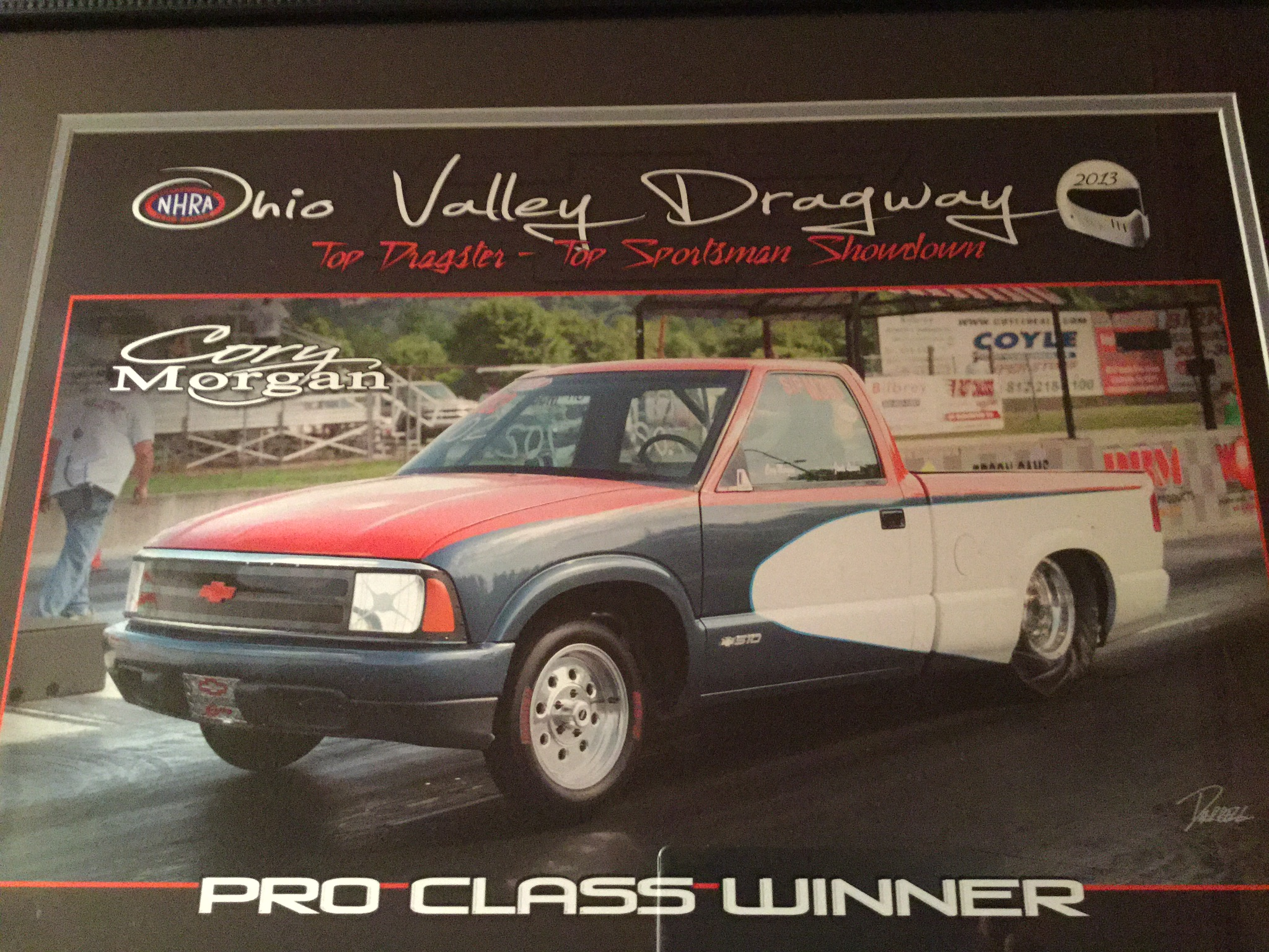 red blue and white 1997 Chevy S10 competing in a drag race in a  frame from Ohio Valley drag way that labels the truck as the pro class winner 2013