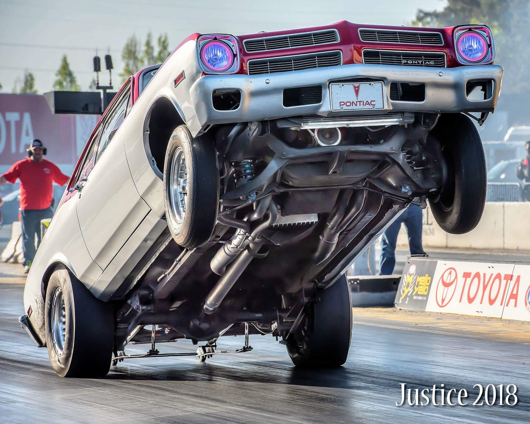 a 192 pontiac ventura doing a wheel stand on a racetrack