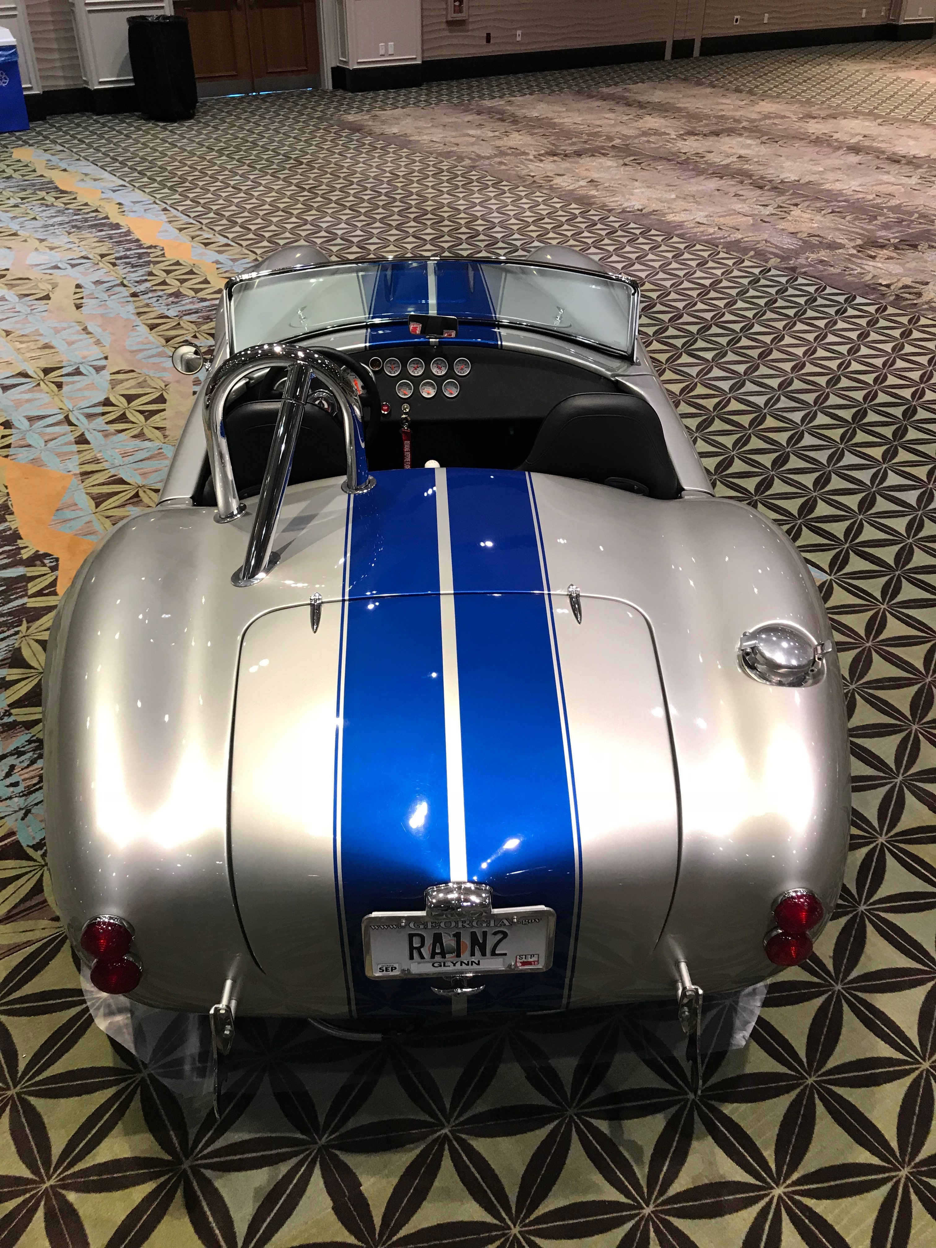 rear of 1965 ac cobra in silver with blue stripes
