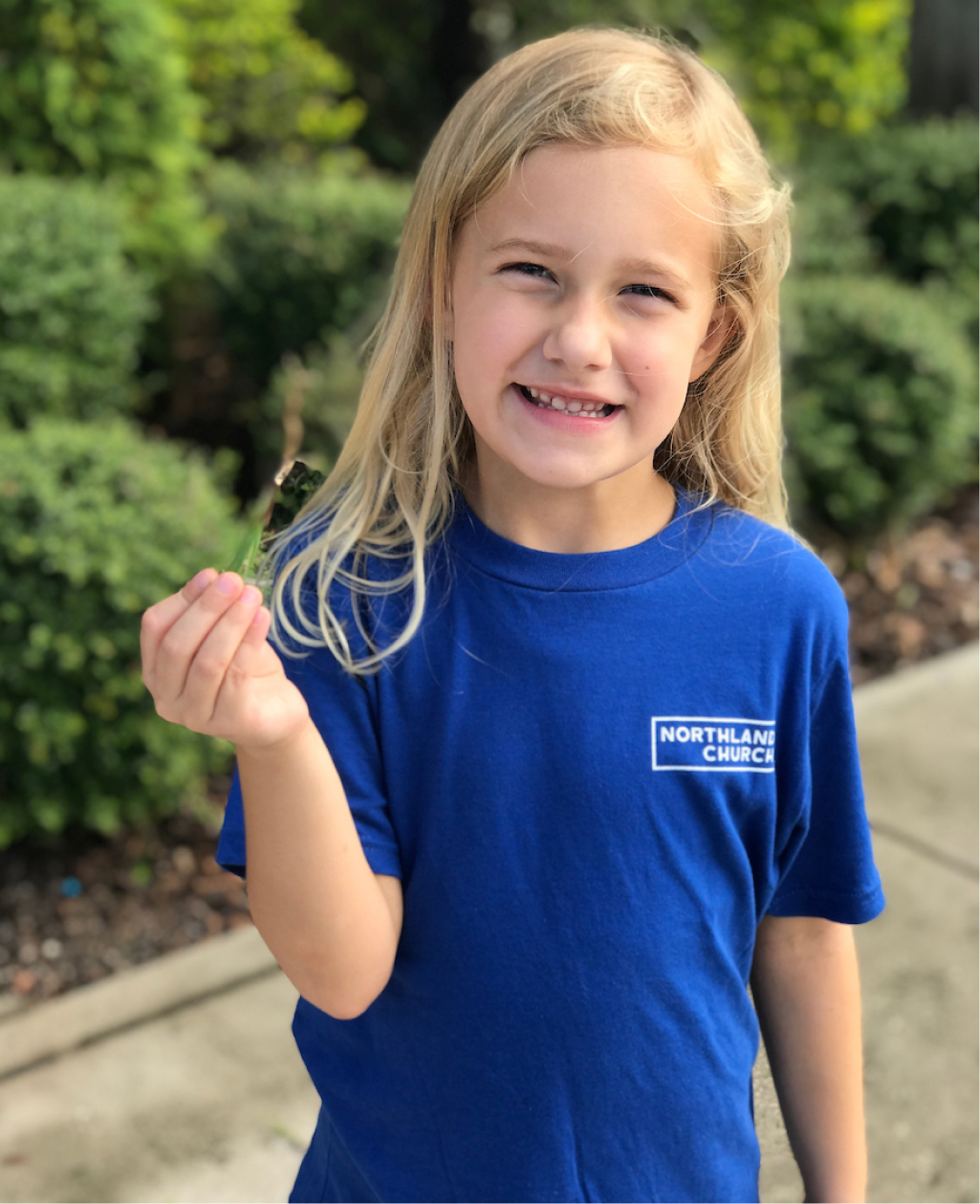 Young girl smiling in blue serve shirt