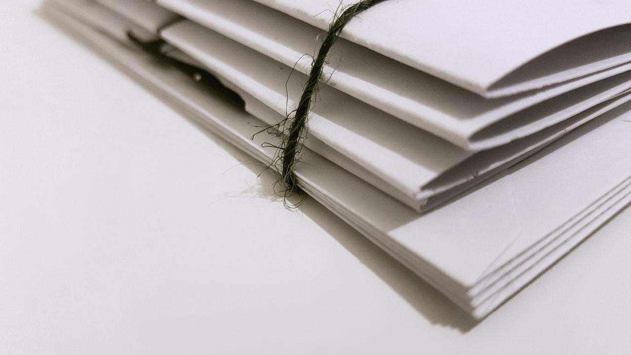 Stack of papers bound together with a thin rope