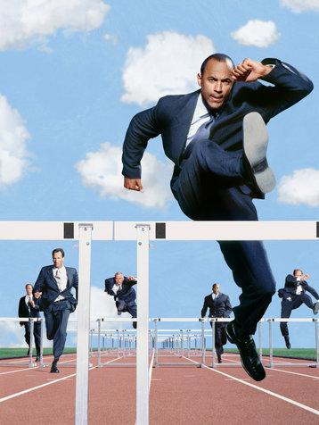 Business man jumping over a hurdle in a track race.