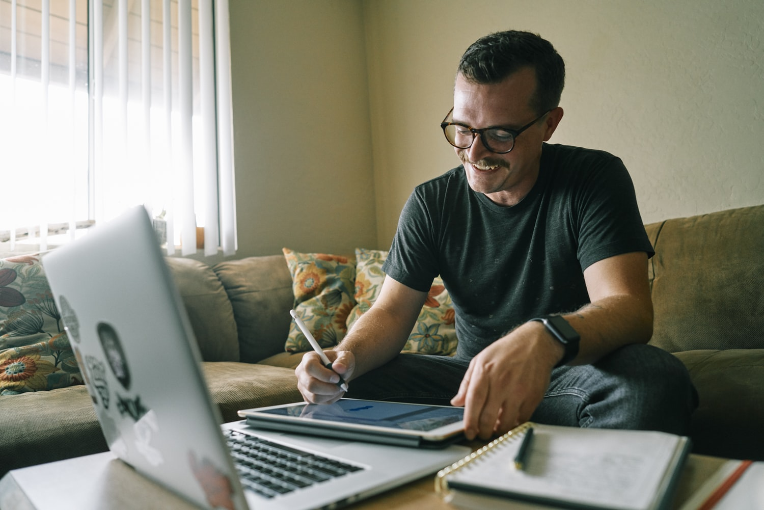 A man smiling and writing.  He is working from home on his couch, with a laptop in the foreground.